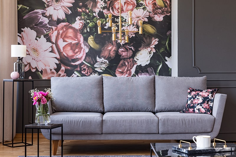 Bohemian style living room wallpaper designs with a large floral prints in a pink and black combination lends a bohemian