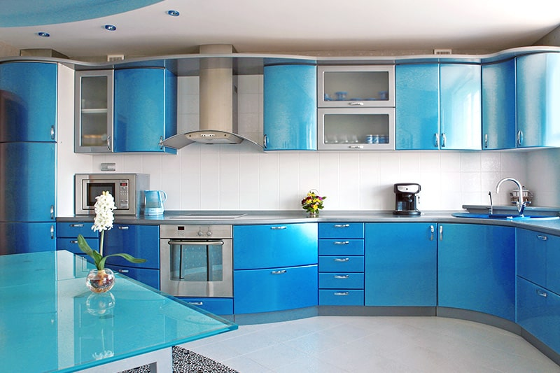 Blue kitchen cupboards with smooth curves to resemble fluidity of ocean w waves