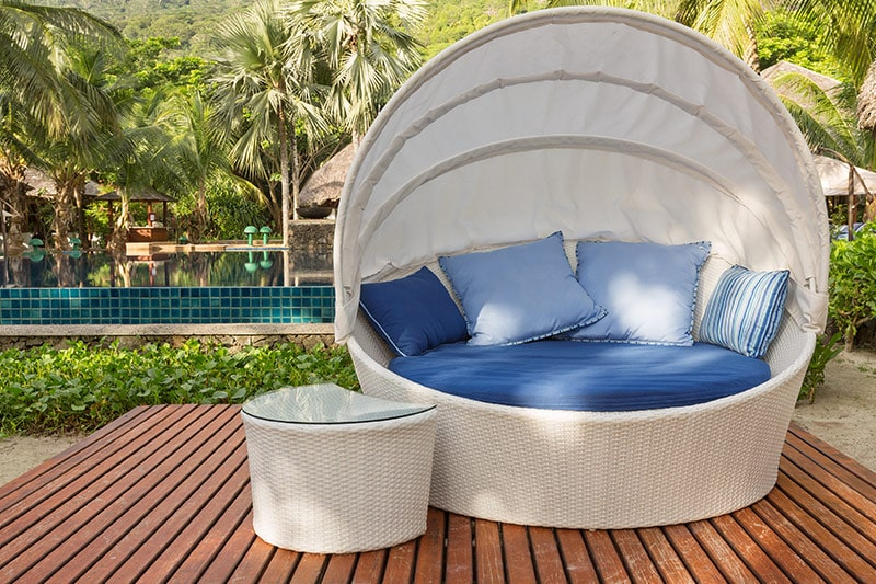Outdoor lounge design with a round canopy chair in white