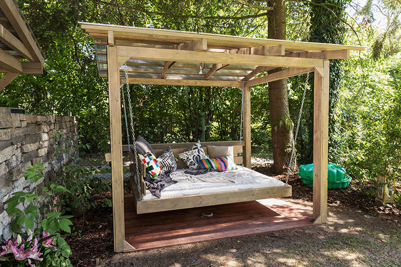 Outdoor garden design with a swing daybed and plenty of pillows