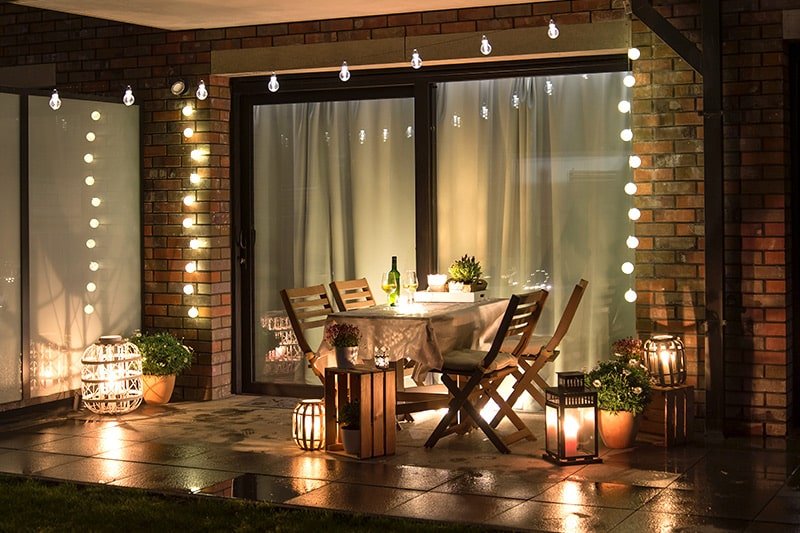 Outdoor lighting design with fairy lights and candle lights on the table and outdoor wall design with magic lights
