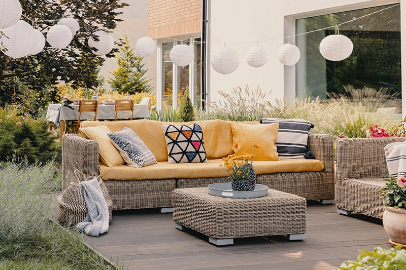 Home outdoor design by separating seating and dining spaces of a large outdoor area