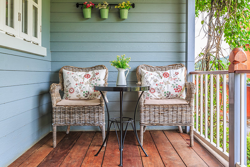 Simple outdoors design with a wicker chairs in a wooden veranda