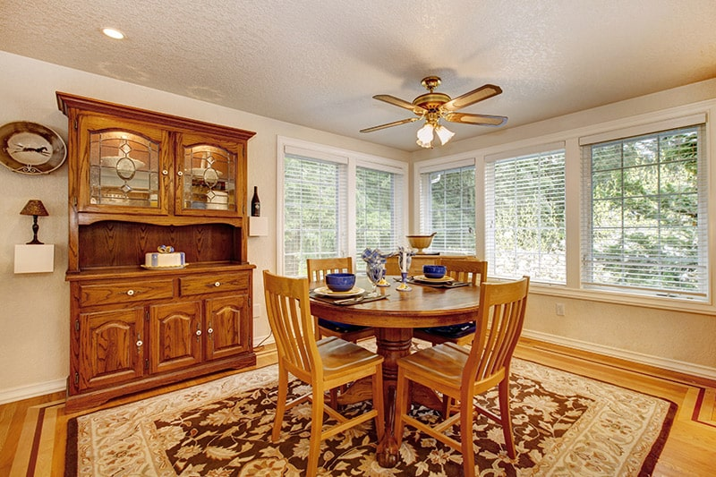 Wooden dining room cabinet made with polished wood and gives warm vibe to dining room interior