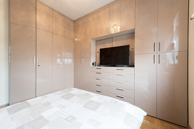 Wardrobe design with tv which is from ceiling to floor and extends across both walls of the bedroom