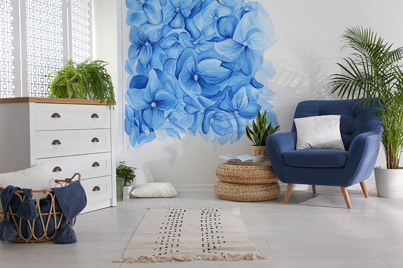The floral carolina blue living room design with blue floral patterns painted on the wall look artistic and stylish