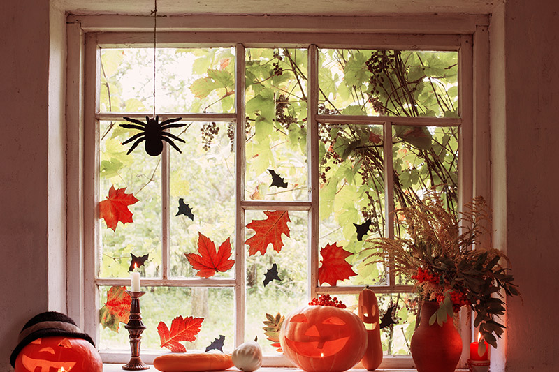 Halloween window decoration ideas add orange and brown leaves look rustic and blend in well with pumpkins.