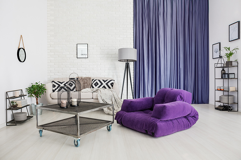 Purple colour room with a purple curtain and a purple sofa with modern and minimal furniture